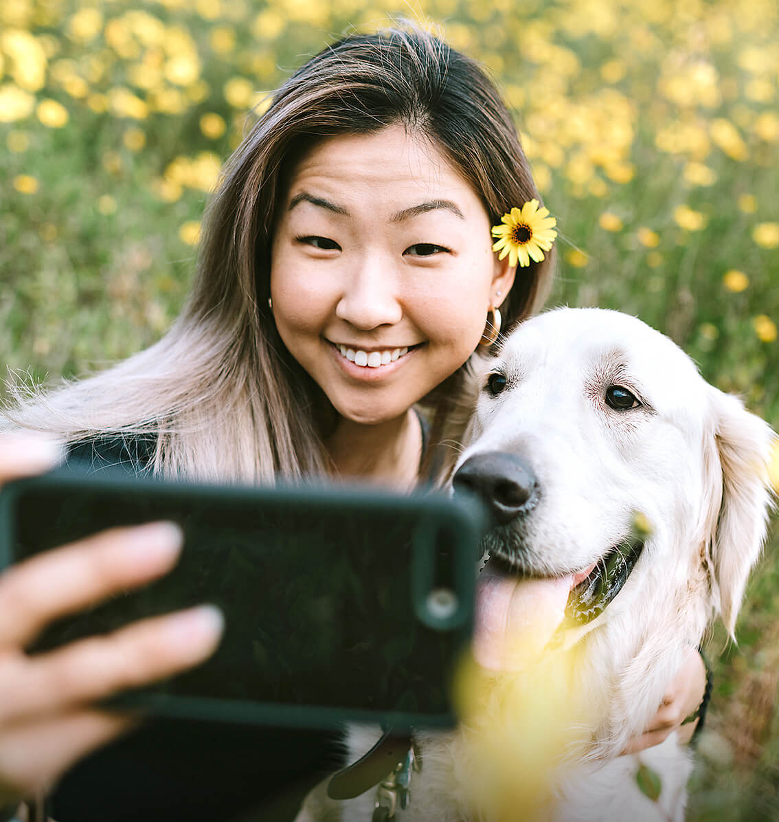 woman taking a photo with a golden retriever