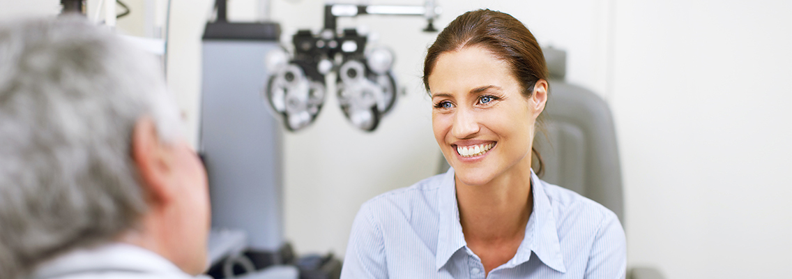 woman smiling with an eye care practitioner